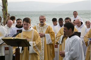 Fr. Pizzaballa, ofm, Custos of the Holy Land, stands behind a deacon proclaiming the Gospel on the shores that Jesus himself spoke the Gospel for the first time.