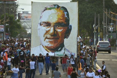People carry a picture of the late Archbishop Romero during a march ahead of the 34th anniversary of his assassination in San Salvador