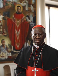 "Nigerian Cardinal Francis Arinze, retired prefect of the Congregation for Divine Worship and the Sacraments, is pictured in front of an image of Blessed Cyprian Michael Tansi in his residence at the Vatican Feb. 12. Cardinal Arinze, who personally heard Pope Benedict XVI's resignation, said ""I have no doubt about his wisdom....He doesn't rush, he is not rash, he is gentle but he is also clearheaded and firm. So it could not have been an idea he got the day before."" (CNS photo/Paul Haring) (Feb. 12, 2013) See BENEDICT-ARINZE Feb. 12, 2013."