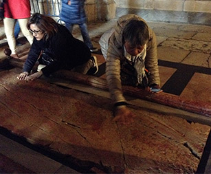 Thelma's sister, Lourdes, and other pilgrims from Thelma's pilgrimage group praying at the Stone of Anointing.
